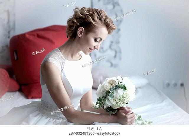 charming beautiful bride holding wedding bouquet in her hands. bride in white dress in a luxury interior lying on the beautiful white bed
