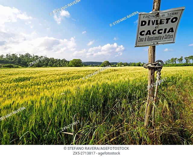 hunting ban sign near wheat fields in the region of Umbria, Italy
