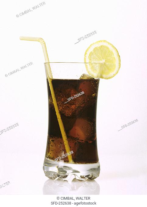 A glass of Cola with ice cubes, slice of lemon and straw