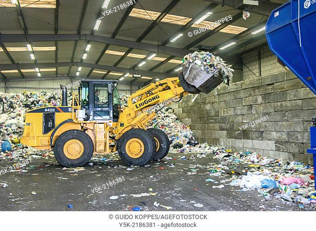 Tilburg, Netherlands. Large shovel processing plastic waste in a recycling center, after collecting it at local households