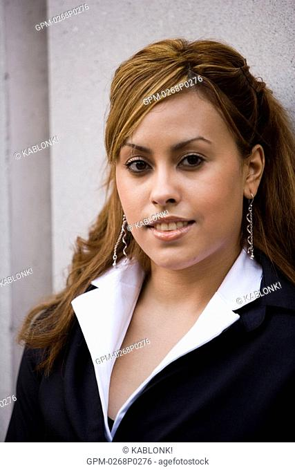 Heashot of Hispanic businesswoman smiling outside office building