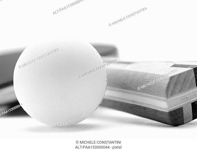Ping pong paddle and ball, close-up, b&w