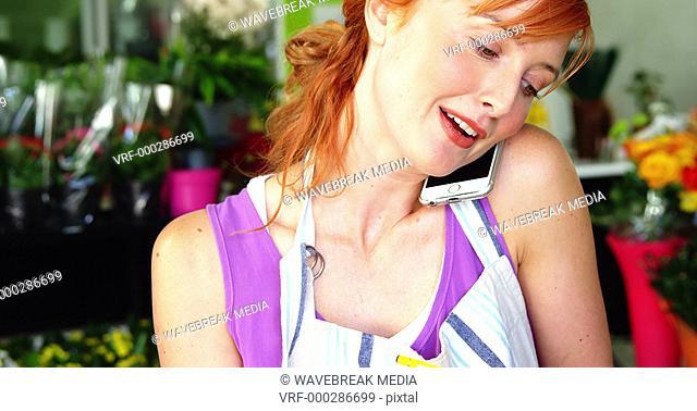 Female florist taking order on mobile phone