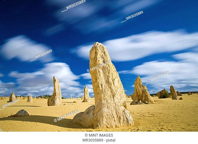 Desert landscape dotted with limestone pinnacles under a cloudy sky