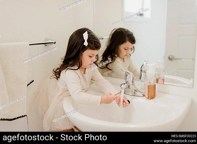 Girl washing hands in bathroom
