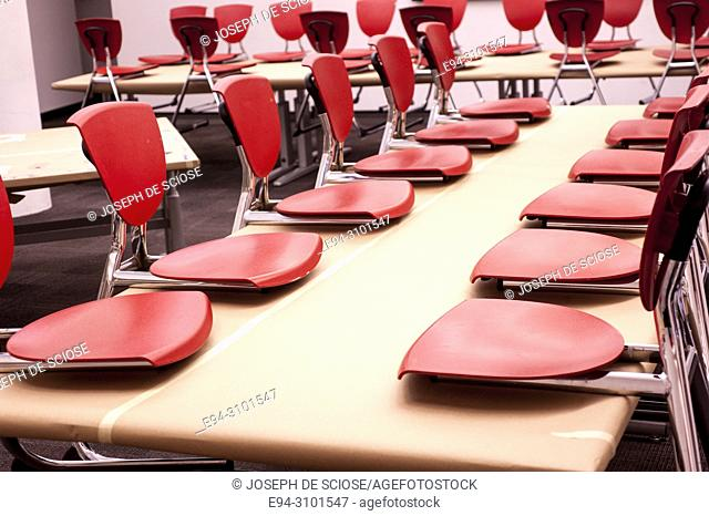 Orange plastic and metal children's chairs placed on a table top in a classroom creating a graphic design