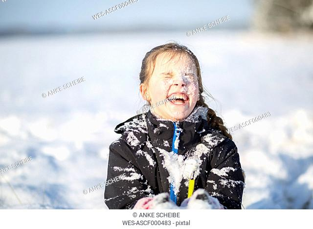 Portrait of laughing girl with snow-covered face