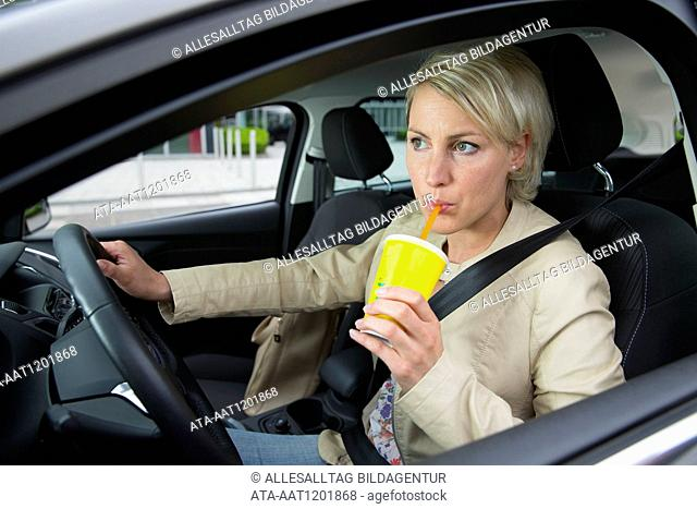 Female car driver is drinking a juice