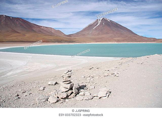 Beautiful volcano landscape with a green lagoon in Andes of Bolivia