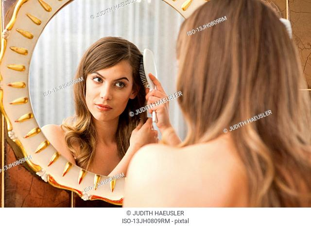 woman crewing out in front of mirror