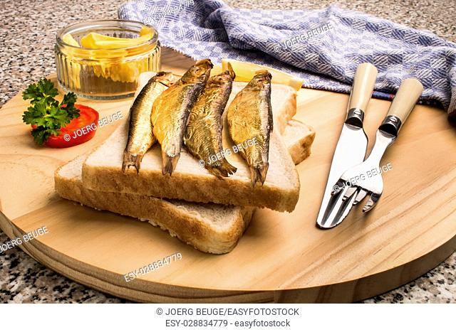 golden brown smoked sprats with toast bread, butter and slice tomato on wooden board