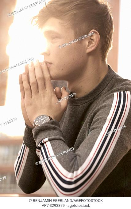 young model man with folded hands, side view, in Hamburg, Germany