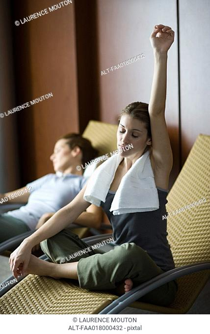 Two women relaxing on lounge chairs, one sitting indian style with arm up and eyes closed