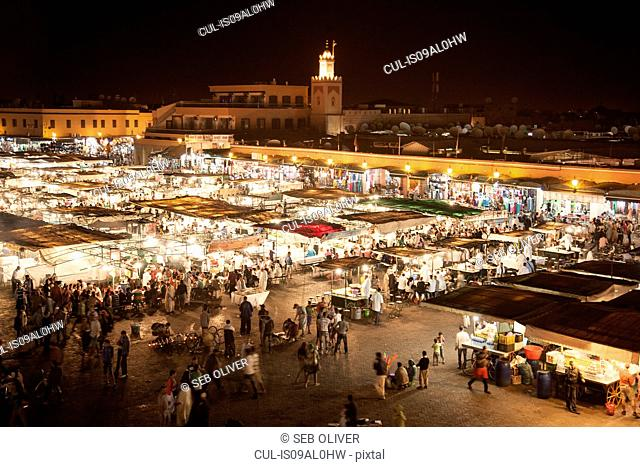 View of crowds of shoppers and market stalls at night, Jamaa el Fna Square, Marrakech, Morocco