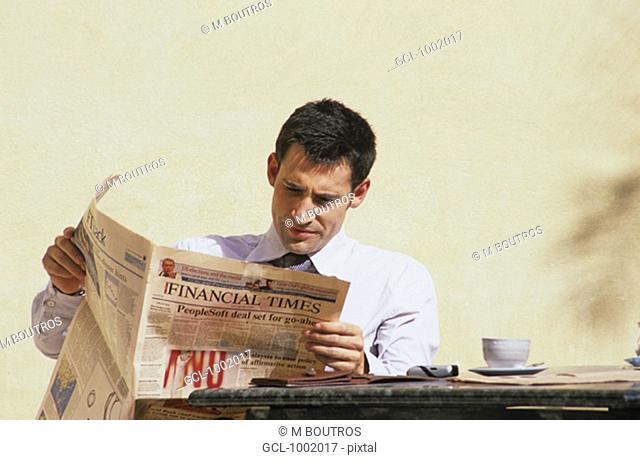 Businessman reading newspaper during a coffee break
