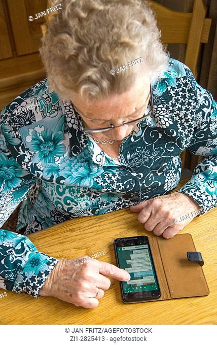 old woman at table with smartphone