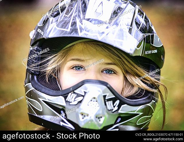 Young blond girl in a motorcycle helmet outdoors