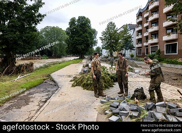 16 July 2021, Rhineland-Palatinate, Bad Neuenahr: Three muddy soldiers take a break from work while the river Ahr can be seen in the background