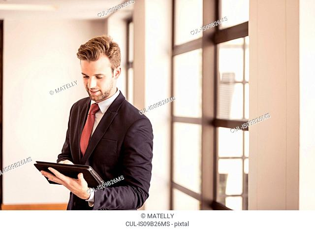 Young businessman using digital tablet touchscreen in office