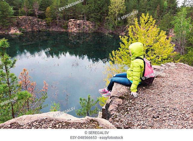 Hipster young girl with backpack enjoying the view of the lake on peak of foggy mountain among the pine forest. Tourist traveler