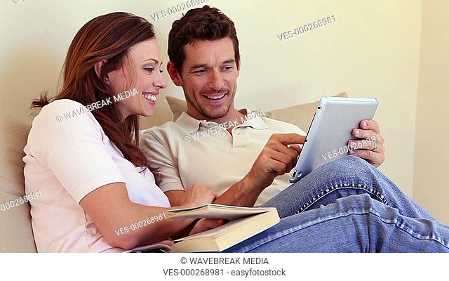Happy couple sitting on sofa using tablet pc together