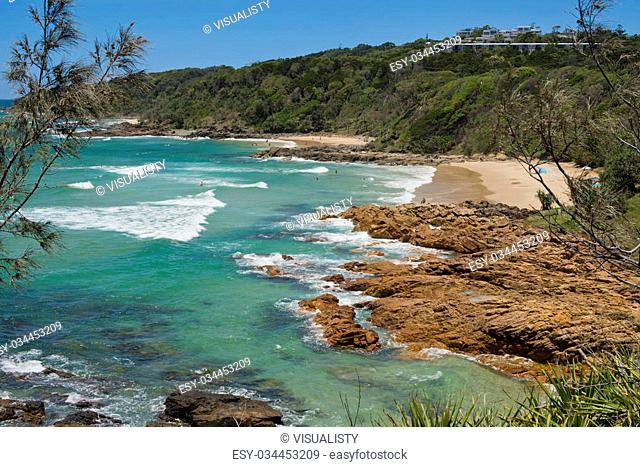 Rocky and sandy bay at Coolum, Queensland, Australia near Point Arkwright. White breaking surf with some swimmers. Beautiful sunny day with clear blue sky