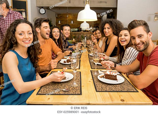 Multi-Ethnic Group of happy friends lunching and tasting the dessert at the restaurant