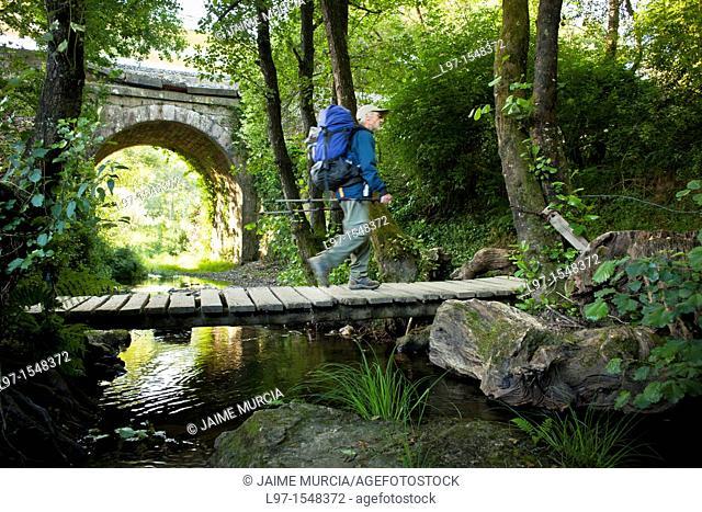 Pilgrim crossing over small wooden bridge along the Camino de Santiago, near the city of Sarria