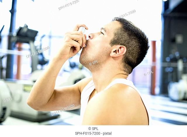 MODEL RELEASED. Young man using inhaler in gym