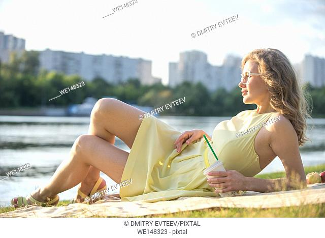 Woman is getting picnic on a blanket in a city park at pond shore