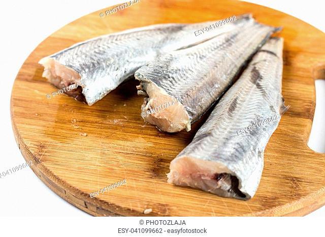 Fresh hake fish on the wooden board