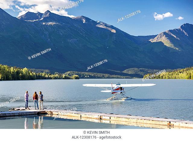 Visitors watch a float plane depart, Trail Lake Float Plane Base, Moose Pass, Kenai Peninsula, Southcentral Alaska, USA