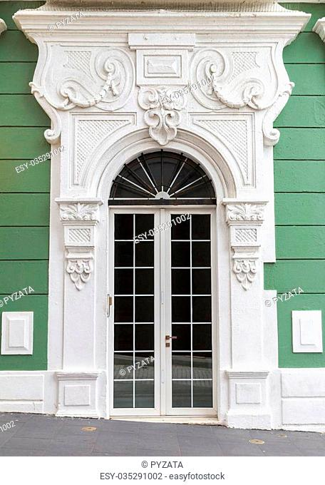 Renovated charming old Spanish door with decorative portal over green wall in San Juan, Puerto Rico