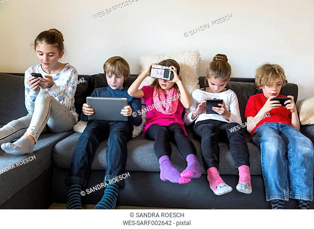 Group picture of five children sitting on one couch using different digital devices