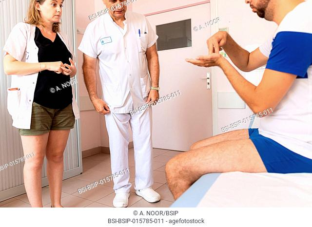 Care for deaf patients in sign language, Nice Hospital, France. A young deaf man suffering from venous insufficiency. He has had an operation on one leg but...