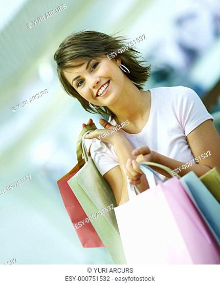 Portrait of a attractive young woman holding shopping bags