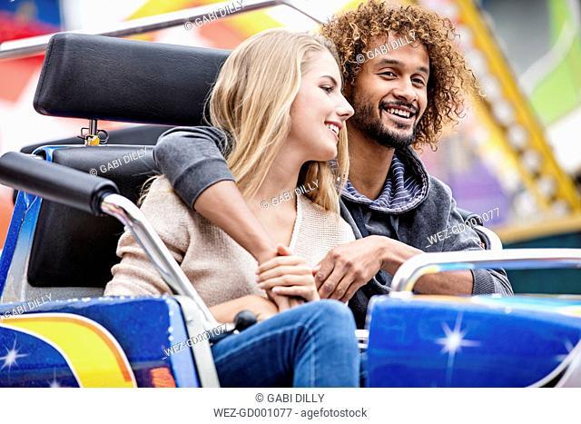 Happy couple on a carousel at a fun fair