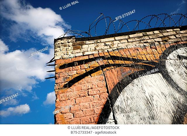Brick warehouse corner, with graffiti and barbed wire. East End, London, England