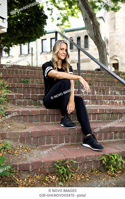 Young Adult Woman in Fitness Attire Sitting on Brick Stairs Outdoor