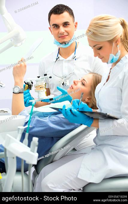 Young dentist working with the patient in a modern hospital. He is assisted by a young girl assistant. The patient sees in the mirror the result of the work of...