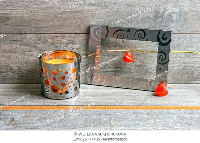 Metal frame with clematis fruits and candlestick with orange candle on a rough gray wooden background with gift ribbon