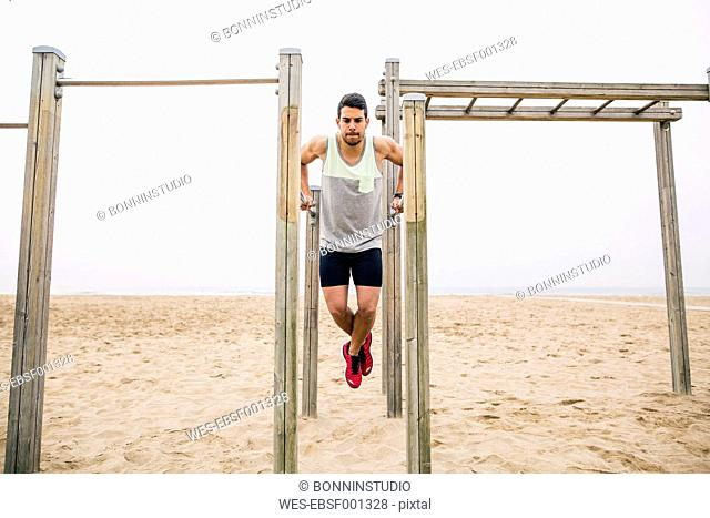 Young man exercising on bars on the beach