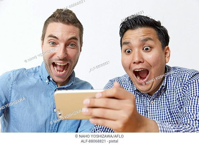 Multi-ethnic men using smartphone