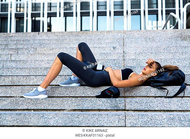 Sportive young woman wearing boxing gloves lying on stairs in the city