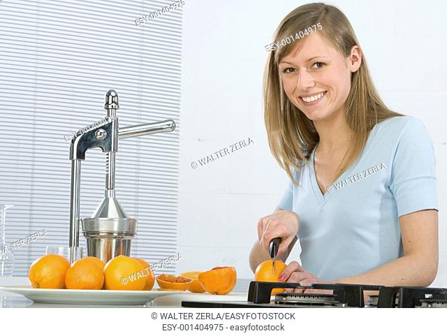 Beautiful girl in the kitchen with juicy orange