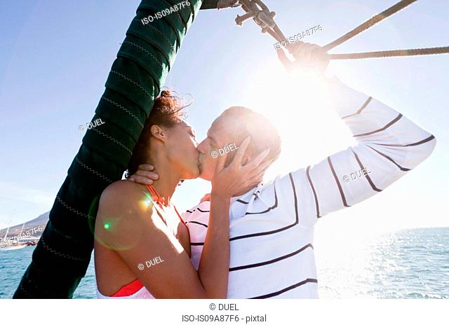 Young couple on yacht, kissing