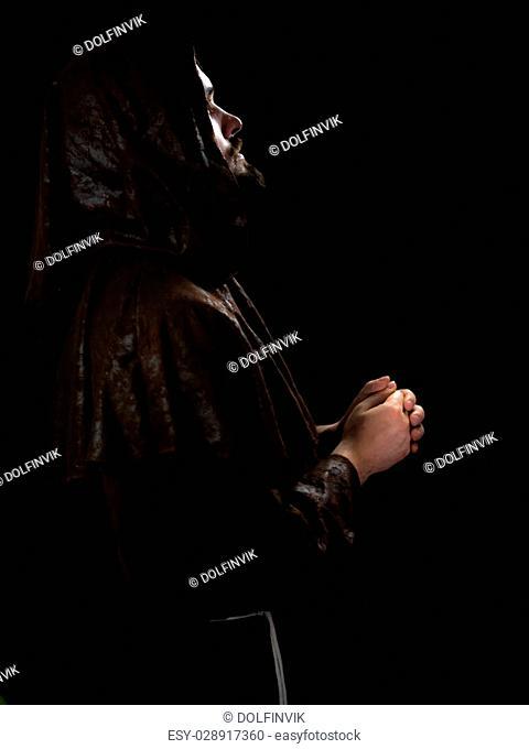 mysterious monk on dark background. studio shot