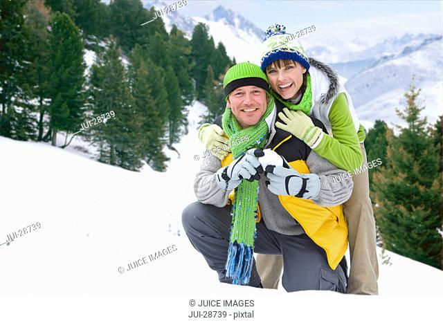 Smiling couple standing in snow holding snowball