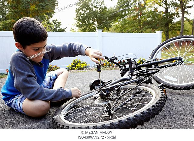 Determined boy repairing bicycle on driveway