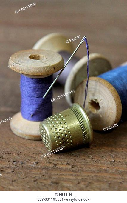 The coil of blue thread with a needle stuck